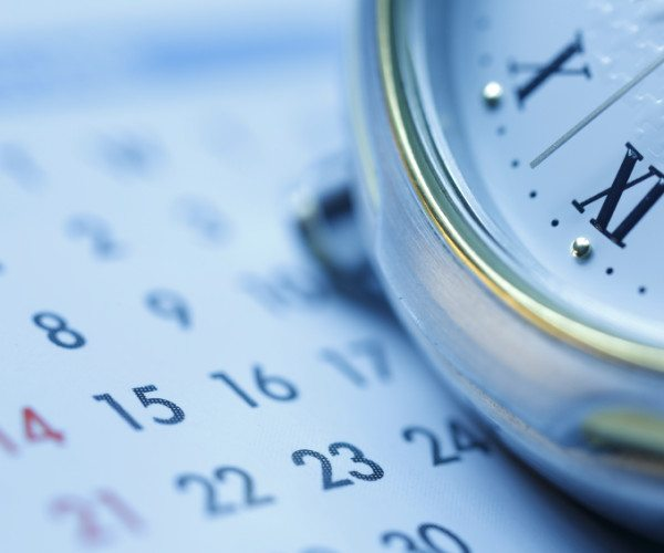 A pocket watch sitting on a calendar. Shot with shallow depth of field Blue tone