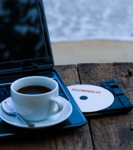 Coffee cup and laptop on old wood table on the beach summer concept