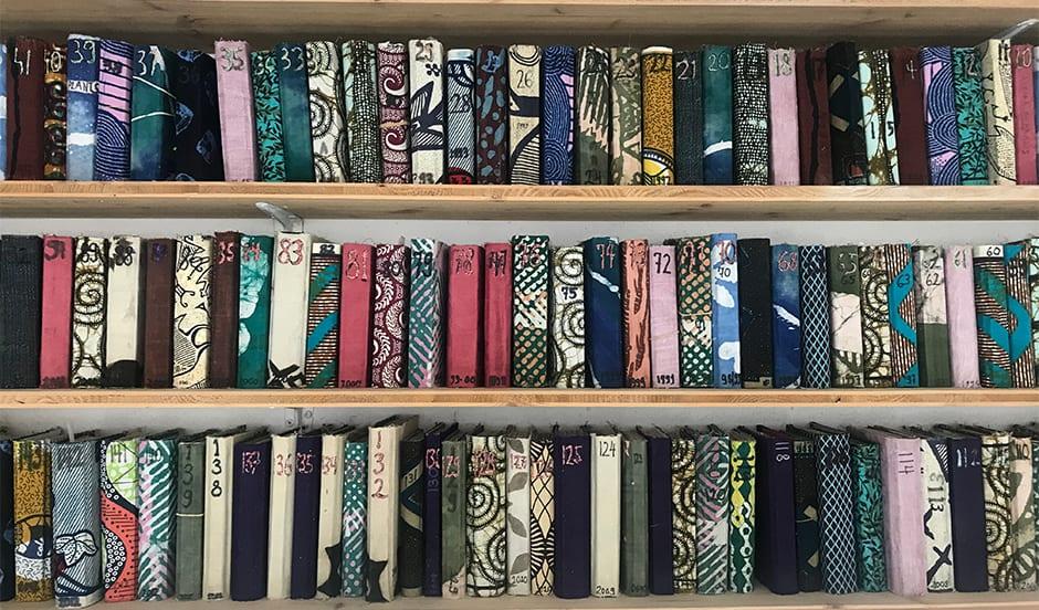 carnets d'artistes alignés sur une étagère